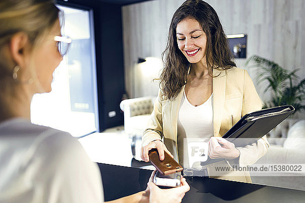 Smiling businesswoman paying contactless with smartphone at reception