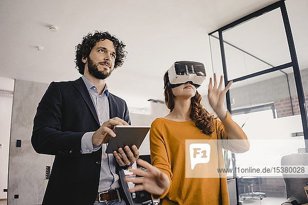 Businessman and businesswoman with VR glasses and tablet in office