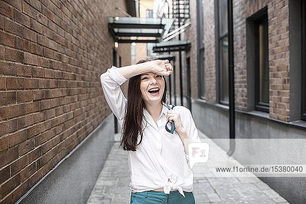 Porträt einer lachenden Frau in der Stadt