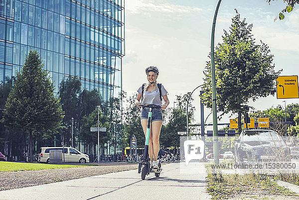 Junge Frau fährt E-Scooter auf Bürgersteig  Berlin  Deutschland