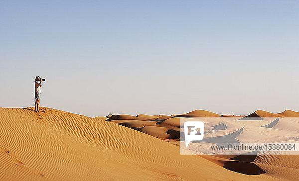 Mann beim Fotografieren in der Wüste  Wahiba Sands  Oman