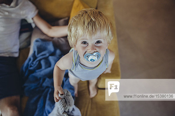 Little boy with pacifier standing on couch,  looking up at camera