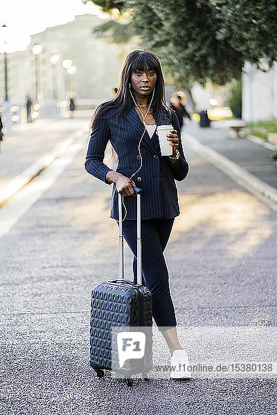 Porträt einer Geschäftsfrau mit Koffer und Kaffee zum Draussengehen