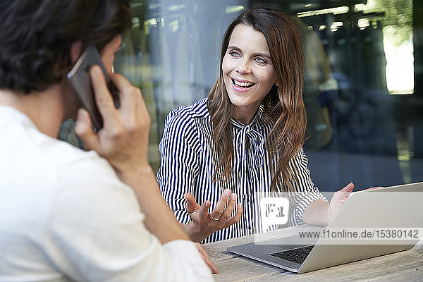 Businesswoman with laptop and man on cell phone in the city