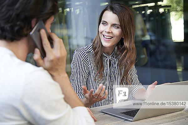 Geschäftsfrau mit Laptop und Mann am Handy in der Stadt
