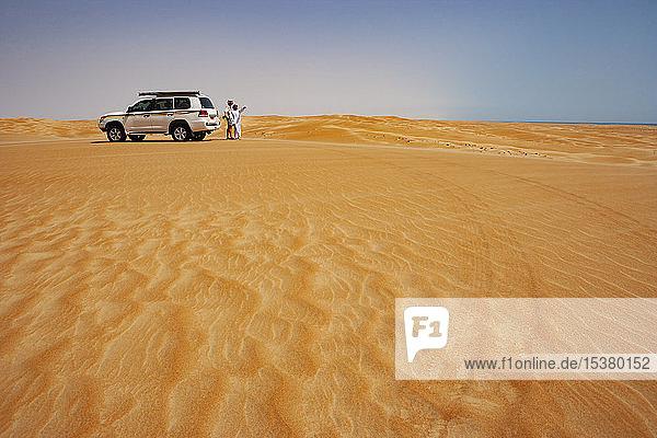 Tourist im Gespräch mit seinem Fahrer in der Wüste neben dem Geländewagen,  Wahiba Sands,  Oman