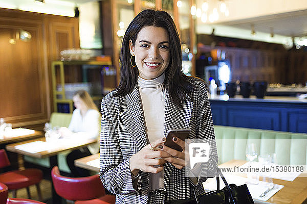 Portrait of smiling businesswoman holding cell phone in a restaurant
