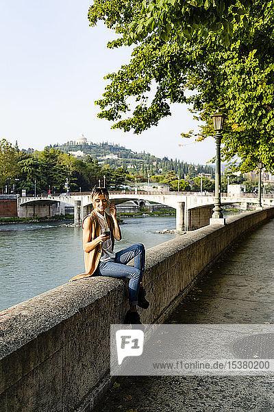 Frau mit Kopfhörern sitzt mit Smartphone am Flussufer