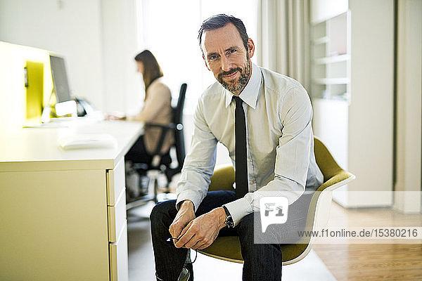 Porträt eines selbstbewussten Geschäftsmannes im Amt mit Mitarbeiter im Hintergrund