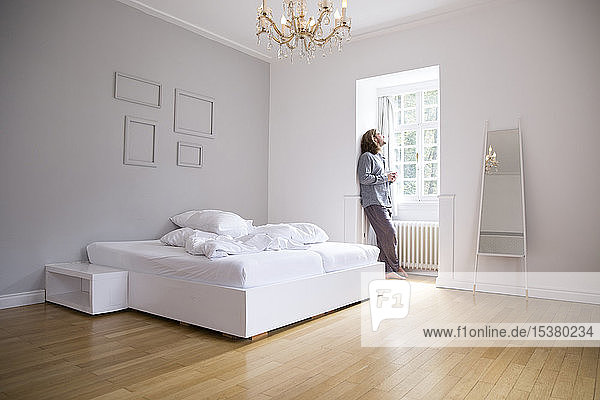 Junger Mann in Pyjama steht am Fenster im Schlafzimmer