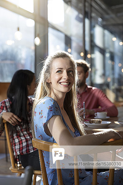 Portrait of smiling woman with friends in a cafe