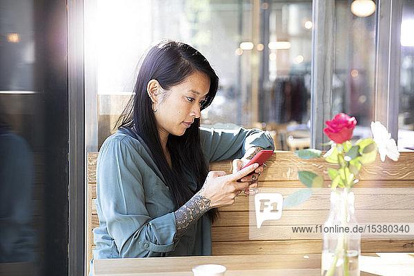 Frau benutzt Mobiltelefon in einem Cafe
