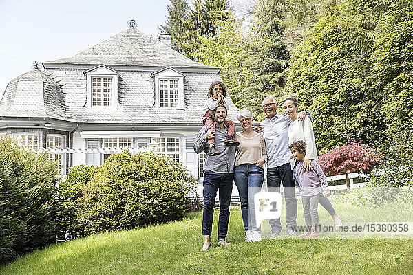 Happy extended family standing in garden of their home