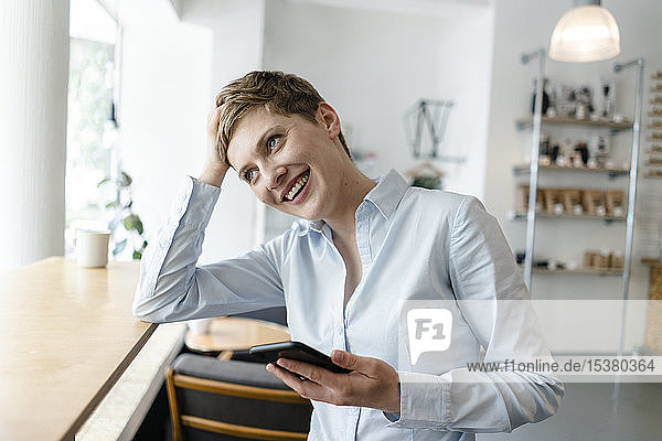 Happy businesswoman with cell phone in a cafe