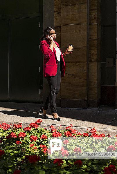 Junge Geschäftsfrau mit Kaffee zum Telefonieren  London  UK