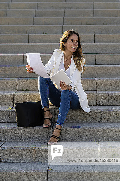 Businesswoman sitting on stairs with paper and tablet