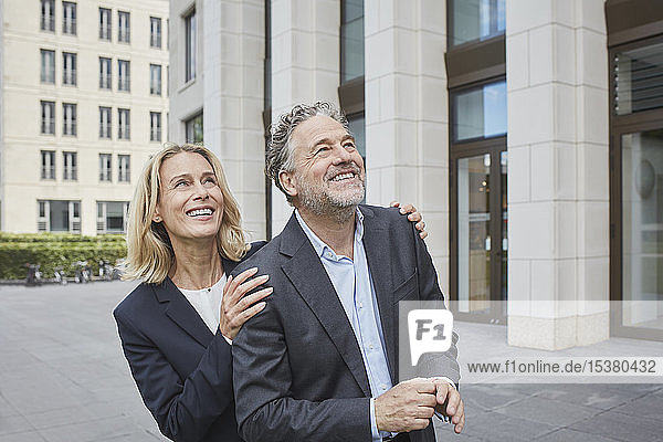 Happy businessman and businesswoman in the city looking up