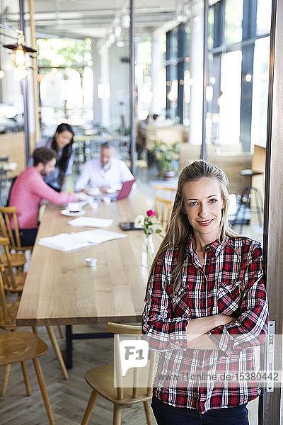 Porträt einer ungezwungenen Geschäftsfrau in einem Cafe mit Kollegen,  die im Hintergrund eine Besprechung abhalten