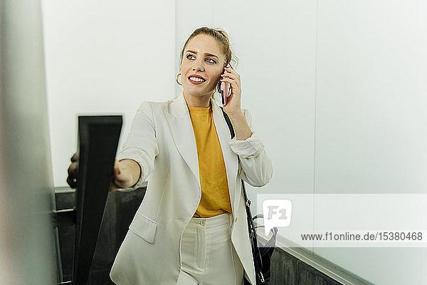 Geschäftsfrau in weißem Hosenanzug  Treppensteigen  Smartphone benutzen