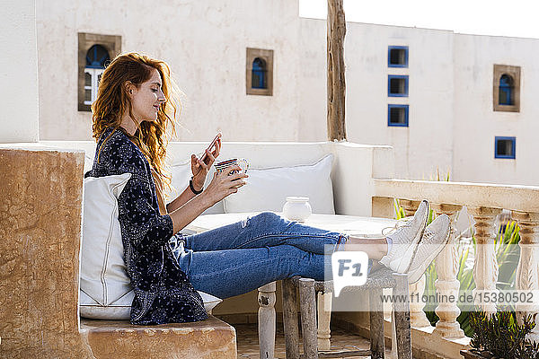 Smiling redheaded young woman relaxing with cup of coffee on roof terrace looking at cell phone