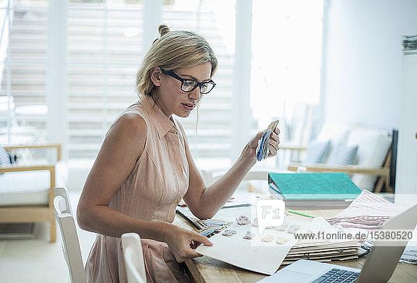 Frau mit Laptop arbeitet an Modedesigns auf dem Tisch