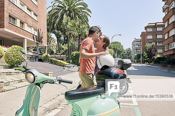 Young couple kissing at a vintage motor scooter