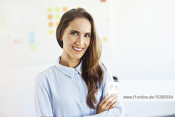 Junge Geschäftsfrau steht im Büro und lächelt in die Kamera