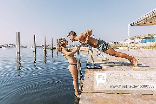 Junges Paar auf einer Mole am Meer