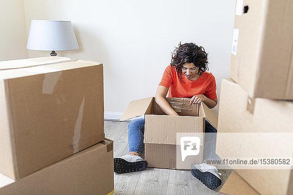 Frau zieht um und schaut neu in den Karton