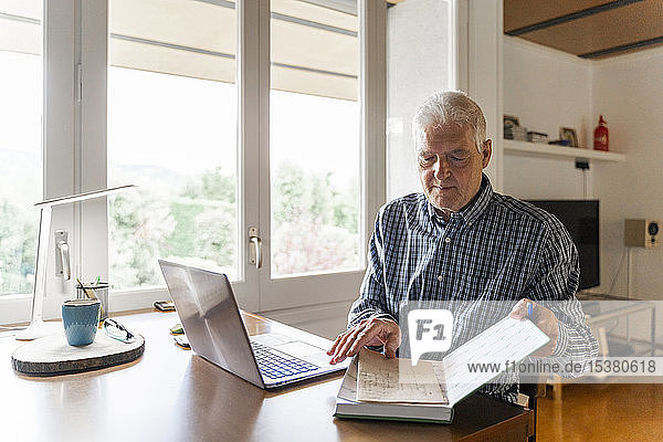 Senior man sitting at home in front of laptop turning pages in notebook