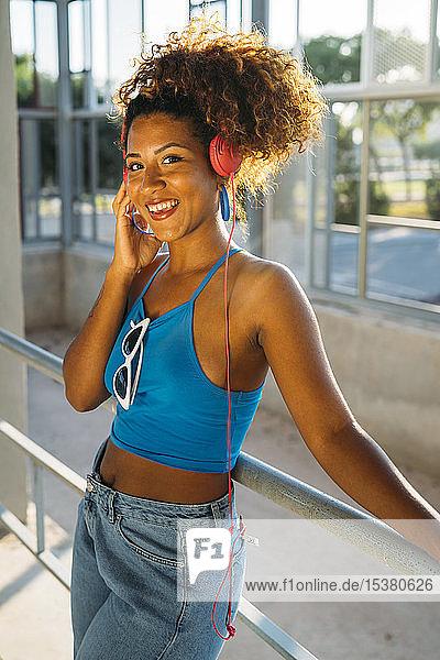 Porträt einer lächelnden jungen Frau  die mit Kopfhörern Musik hört