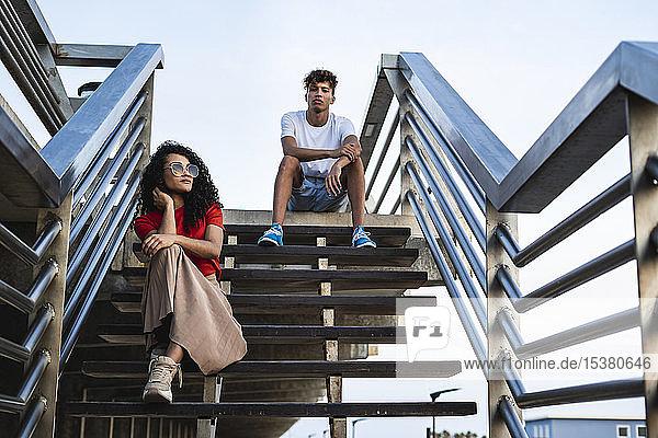 Entspanntes Paar macht eine Pause  sitzt auf einer Treppe in der Stadt Entspanntes Paar macht eine Pause, sitzt auf einer Treppe in der Stadt