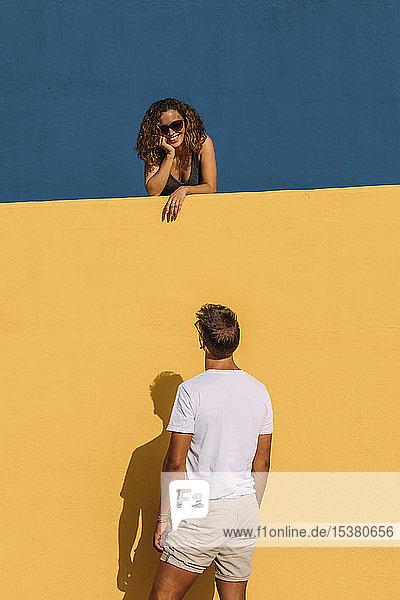 Junger Mann sieht Frau hinter einer gelben Wand an