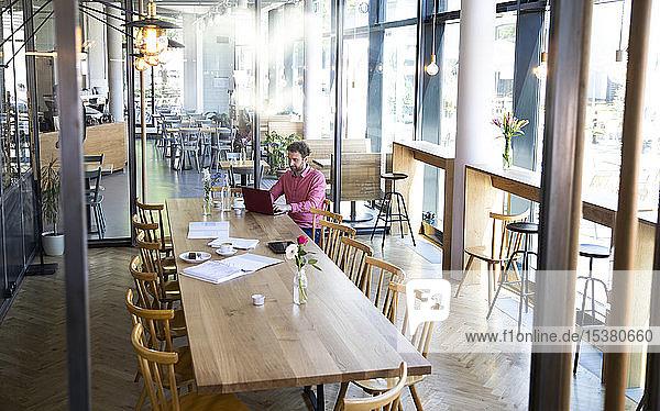 Junger Mann mit Laptop am Holztisch in einem Café
