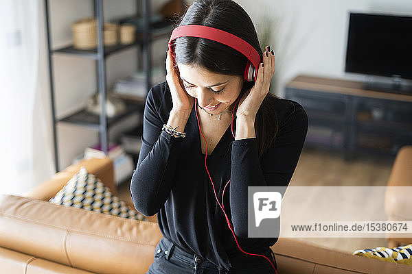 Smiling young woman listening music with headphones at home