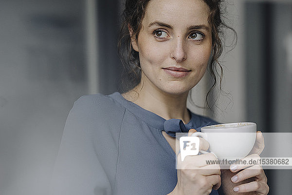 Portrait of young woman relaxing with cup of coffee