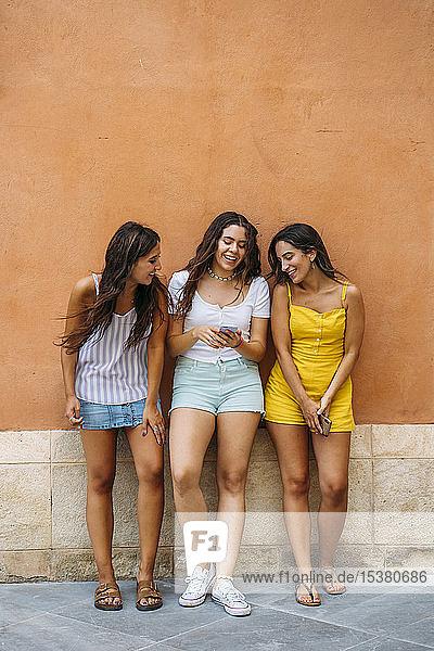 Drei glückliche Freundinnen stehen an einer Wand und teilen sich ein Smartphone