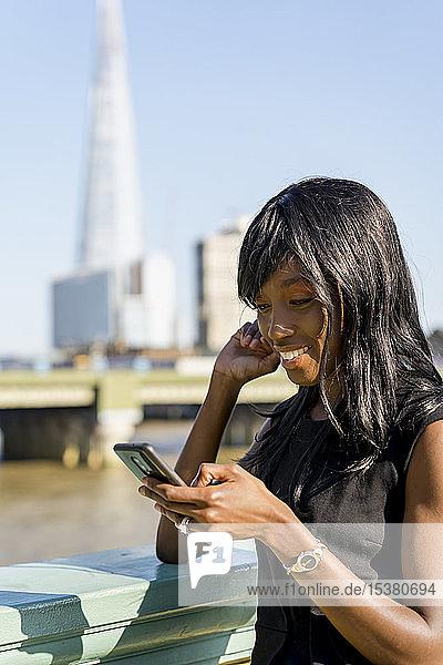 Geschäftsfrau mit Smartphone in der Stadt