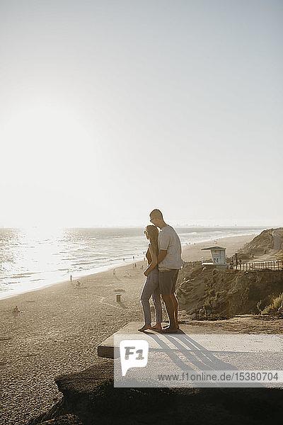 Liebenswertes junges Paar genießt den Blick auf den Strand bei Sonnenuntergang