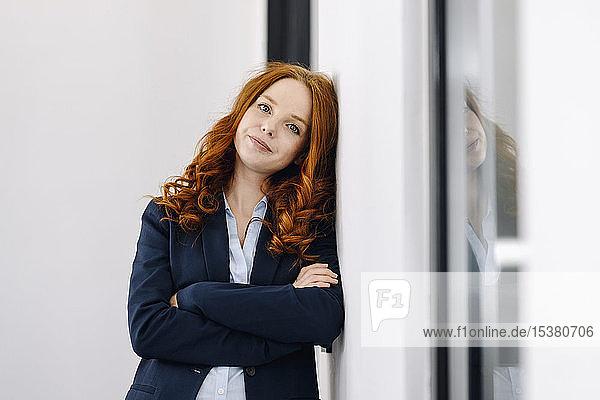 Porträt einer rothaarigen Geschäftsfrau  die an einer Wand lehnt