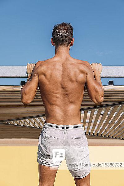 Rückansicht eines sportlichen jungen Mannes in Shorts
