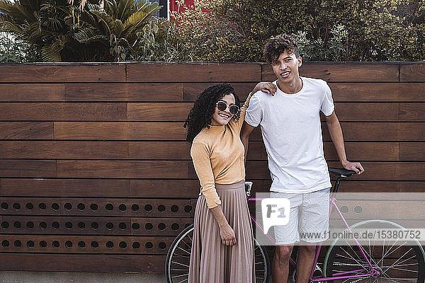 Glückliches Paar mit Fahrrad  an der Wand stehend Glückliches Paar mit Fahrrad, an der Wand stehend