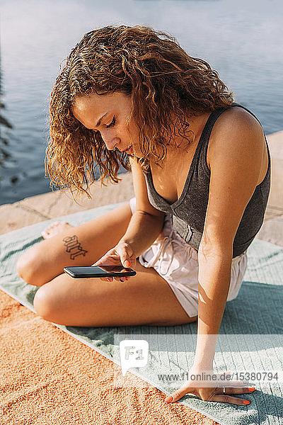 Junge Frau sitzt auf einem Pier am Meer und benutzt ein Smartphone
