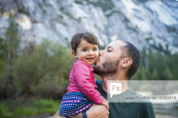 Portrait of happy baby girl kissed by her father  Yosemite National Park  California  USA