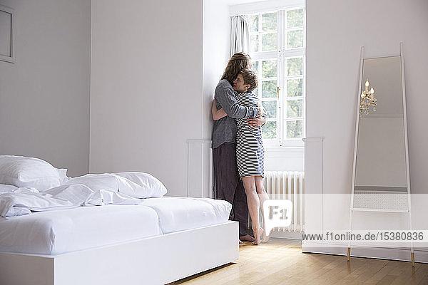 Junges Paar umarmt sich zu Hause am Fenster im Schlafzimmer
