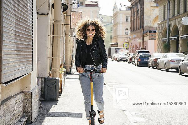 Porträt eines lächelnden Teenager-Mädchens auf einem Roller auf dem Bürgersteig