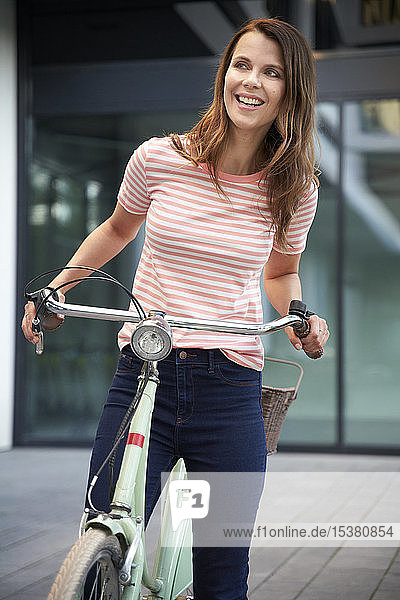 Glückliche Frau mit Fahrrad in der Stadt