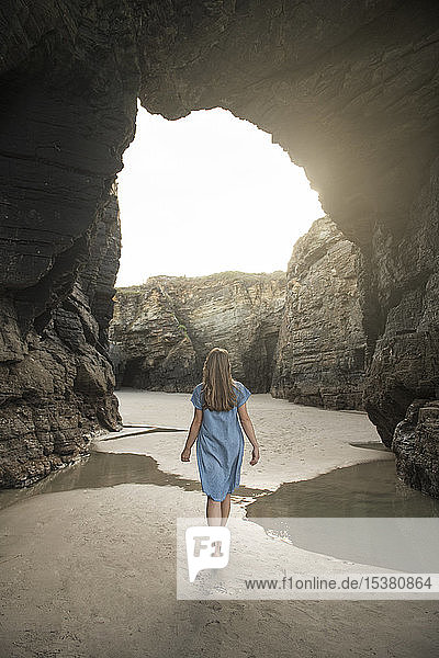 Woman walking on Cathedrals Beach with rocks  rear view  Galicia  Spain