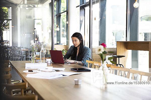 Frau mit Laptop am Holztisch in einem Café