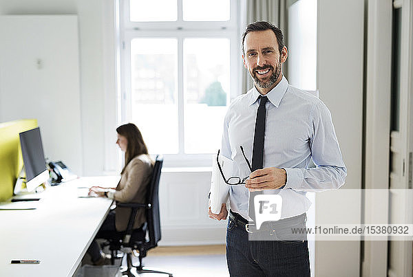 Portrait of smiling businessman in office with employee in background